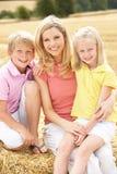 Mutter und Kinder, die auf Stroh-Ballen in Harv sitzen Lizenzfreies Stockfoto