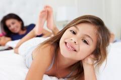 Mutter und Kinder, die in Bett-tragenden Pyjamas sich entspannen Stockfoto