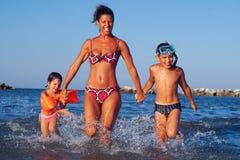 Mutter und Kinder, die in das Meer laufen lizenzfreies stockbild