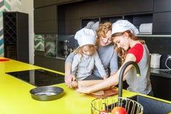 Mutter und Kinder, die in der Küche kochen und Spaß haben lizenzfreies stockbild