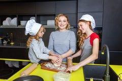Mutter und Kinder, die in der Küche kochen und Spaß haben lizenzfreie stockfotos