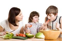 Mutter und Kinder, die an der Küche kochen Lizenzfreie Stockfotos