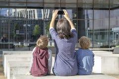 Mutter und Kinder, die draußen selfie Porträt auf Smartphone nehmen Familie, Kindheit, Technologieleutekonzept Lizenzfreie Stockfotografie