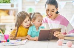 Mutter und Kinder, die ein Buch lesen Stockfotografie