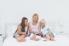 Mutter und Kinder, die eine Zeitschrift lesen Stockfotos