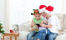Mutter und Kinder, die einen Weihnachtskalender schauen Stockbild