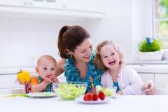 Mutter und Kinder, die in einer weißen Küche kochen Lizenzfreie Stockfotos