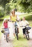 Mutter und Kinder, die Fahrräder in der Landschaft reiten