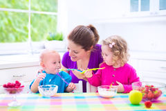 Mutter und Kinder, die frühstücken Lizenzfreie Stockfotografie