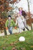 Mutter und Kinder, die Fußball im Garten spielen Lizenzfreie Stockfotos