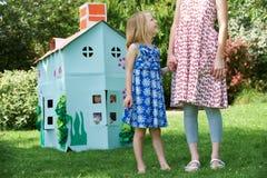Mutter und Kinder, die mit gemachtem Papphaupthaus spielen Stockbilder