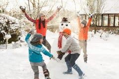 Mutter und Kinder, die Schneemann im Garten aufbauen Lizenzfreie Stockfotos