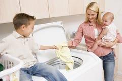 Mutter und Kinder, die Wäscherei tun Stockbild