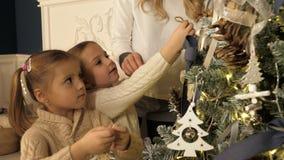 Mutter und Kinder, die Weihnachtsbaum im schönen Familienwohnzimmer mit Kamin verzieren lizenzfreie stockfotografie