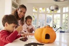 Mutter und Kinder, die zu Hause Halloween-Dekorationen machen lizenzfreie stockfotografie