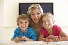 Mutter und Kinder, die zu Hause mit großem Bildschirm fernsehen Stockbild