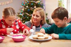 Mutter und Kinder, die zusammen Weihnachtsplätzchen verzieren lizenzfreies stockbild