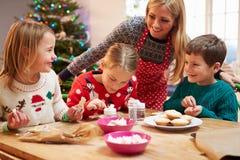 Mutter und Kinder, die zusammen Weihnachtsplätzchen verzieren lizenzfreies stockfoto