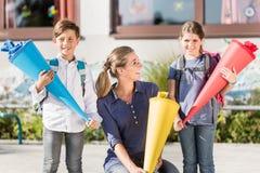 Mutter und Kinder am ersten Tag der Schule mit Süßigkeitskegeln Lizenzfreies Stockbild