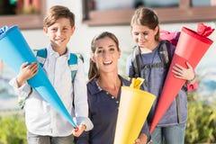 Mutter und Kinder am ersten Tag der Schule mit Süßigkeitskegeln Lizenzfreies Stockfoto