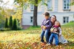 Mutter und Kinder am Herbstpark Lizenzfreie Stockbilder