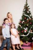 Mutter und Kinder nähern sich einem Tannenbaum Stockbild