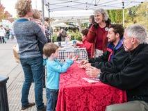 Mutter und Kinder sprechen mit Lebensmittel-Tagesfreiwilligen bei Corvallis F stockbild
