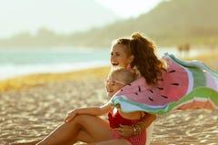 Mutter- und Kinderholdingwassermelonentuch und Haben von Spaßzeit stockfotos