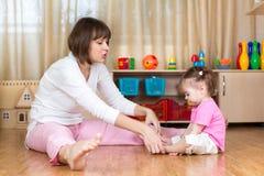 Mutter- und Kinderkinderhandeln gymnastisch zu Hause Lizenzfreie Stockfotos