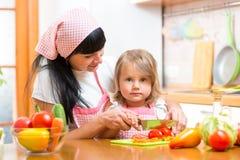 Mutter- und Kindermädchen, das gesundes Lebensmittel zubereitet lizenzfreies stockbild