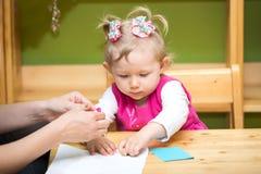 Mutter- und Kindermädchen, das im Kindergarten in Montessori-Vorschule spielt lizenzfreie stockfotos