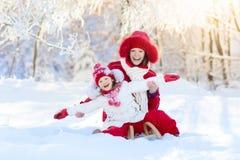 Mutter- und Kinderrodeln Winterschneespaß Familie auf Pferdeschlitten Lizenzfreies Stockbild
