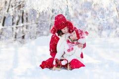 Mutter- und Kinderrodeln Winterschneespaß Familie auf Pferdeschlitten Stockbild