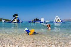 Mutter- und Kinderschwimmen und haben Spaß im Wasser mit aufblasbaren Dias im Hintergrund stockfoto