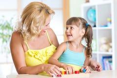 Mutter und Kinderspiel zusammen mit pädagogischem Stockbild