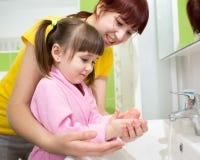 Mutter- und Kindertochter, die ihre Hände im Badezimmer wäscht Sorgfalt und Interesse für Kinder Stockbild