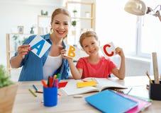 Mutter- und Kindertochter, die zu Hause Hausarbeitschreiben und -lesung tut stockfoto