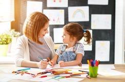 Mutter- und Kindertochter zeichnet in Kreativität im Kindergarten lizenzfreie stockfotografie