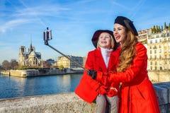 Mutter- und Kindertouristen auf Damm in Paris, das selfie nimmt Stockbild