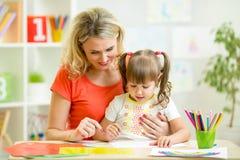 Mutter- und Kinderzeichnung mit Bleistiften zusammen Lizenzfreie Stockfotografie