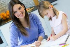Mutter- und Kinderzeichnung mit Zeichenstiften, Sitzen bei Tisch in der Küche Lizenzfreies Stockbild