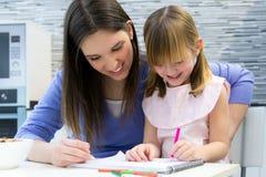 Mutter- und Kinderzeichnung mit Zeichenstiften, Sitzen bei Tisch in der Küche Lizenzfreie Stockfotografie