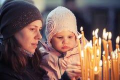 Mutter und kleine blonde kaukasische Tochter in der Kirche Lizenzfreie Stockfotografie