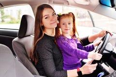Mutter und kleine Tochter, die am Steuer von einem Auto sitzen stockfoto