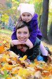 Mutter und kleine Tochter, die unter Herbstlaub liegen Stockbild