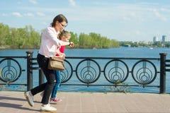 Mutter und kleine Tochter gehen zur Schule Frau betrachtet ihre Uhr, Eilen, ist spät, geht schnell stockfotos