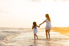 Mutter und kleine Tochter haben Spaß auf dem Strand Stockbilder