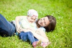 Mutter und kleine Tochter spielen im Park Lizenzfreie Stockfotografie