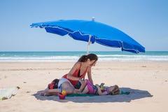 Mutter und kleiner des Mädchens blauer Sonnenschirm unten am Strand Stockfoto