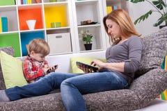 Mutter und kleiner Junge, die mit Tablette und Telefon spielen Lizenzfreie Stockbilder